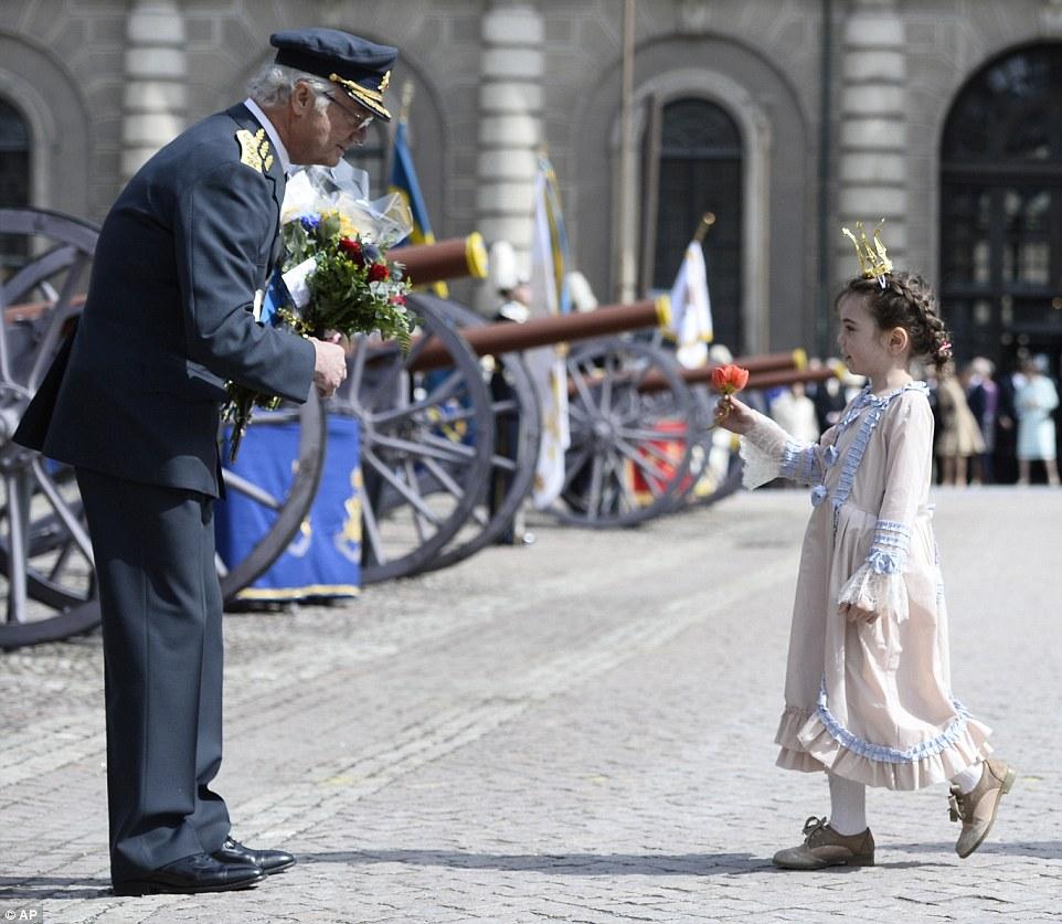 На снимке: во время праздничных мероприятий во внутреннем дворе дворца юная леди в костюме принцессы преподносит королю букет цветов.