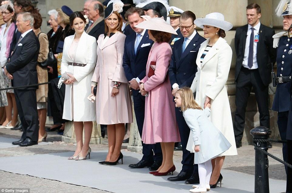 Четырехлетняя малышка, справа, пытается разглядеть происходящее во время парада вооруженных сил Швеции в честь дня рождения монарха.