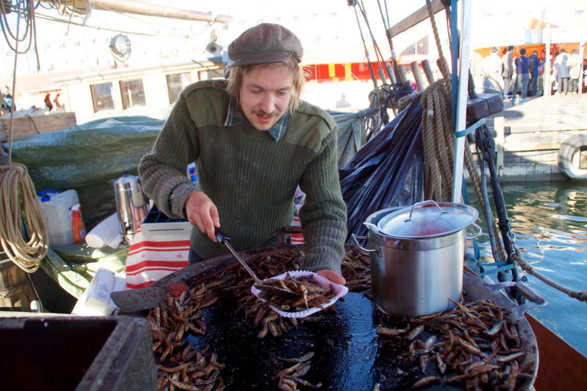 Фото: ScandiNews. Молодой моряк зазывает прохожих отведать жареной рыбы и традиционного сливочного супа лохикейтто на борту двухмачтового парусника «Оlga»
