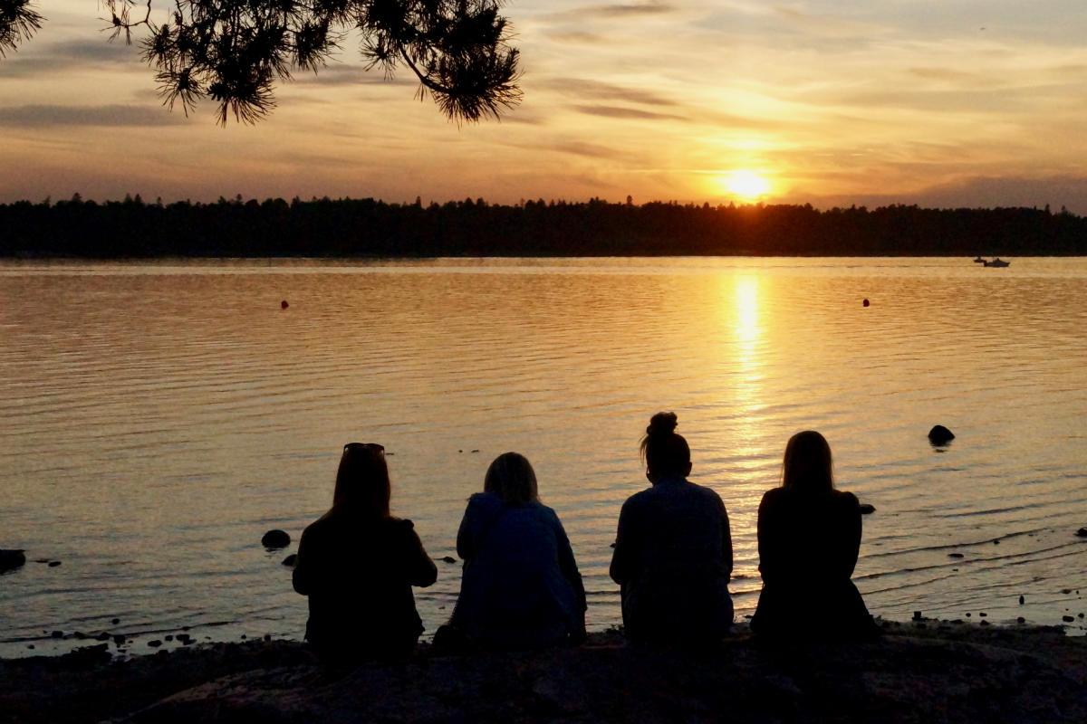Фото: ScandiNews / Девушки в ночь на Миттумаари на берегу озера