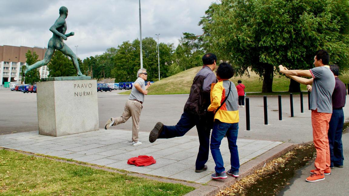 Туристы фотографируются у памятника финскому легкоатлету Павво Нурми в Хельсинки. Фото: ScandiNews